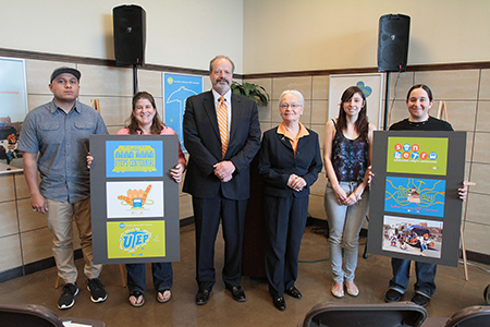 UTEP graphic design students Adrian Bautista, left, [NAME], second from right, and [NAME], right, stand with Associate Professor Anne Giangiulio, El Paso Mayor Oscar Leeser and UTEP President Diana Natalicio during the unveiling of their artwork, which is displayed in Sun Metro's downtown transfer center and on all fixed-route Sun Metro buses. Photo by J.R. Hernandez / UTEP News Service