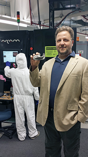 Eric MacDonald, Ph.D., associate director of the W.M. Keck Center for 3-D Innovation, displays a sample of what can be created with a metals printer using the lab's electron beam melting system. MacDonald and Ryan Wicker, Ph.D., the center's director, will be the main editors of a new academic journal, Additive Manufacturing. Photo by Daniel Perez / UTEP News Service.