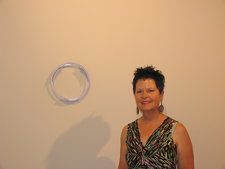UTEP Professor of Art Rachelle Thiewes stands by one of her jewelry pieces on exhibit as part of her retrospective at the Rubin Center. Photo courtesy of the Rubin Center.
