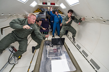 UTEP students Edgardo Flores, middle, and Sergio Cordova, right, float alongside NASA mentor Timothy Pelischek, left, on board a reduced gravity aircraft flight on July 10 in Ellington Field at NASA's Johnson Space Center. Photo courtesy of NASA