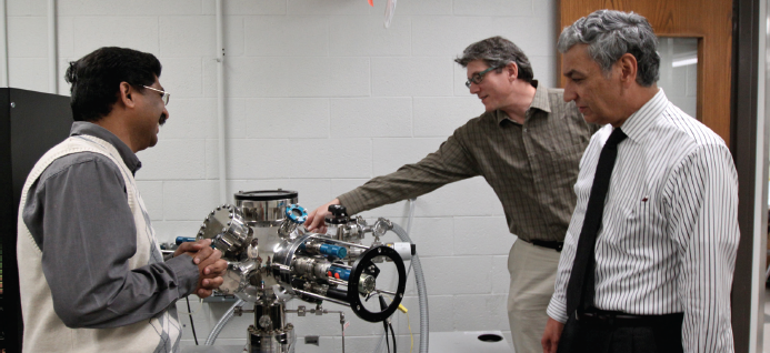 Chintalapalle Ramana, Ph.D., left, demonstrates a sputter-deposition system he developed to fabricate high-temperature coatings. He collaborates with Arturo Bronson, Ph.D., right, and Jack Chessa, Ph.D., to develop coatings designed to withstand temperatures hot enough to liquefy steel.