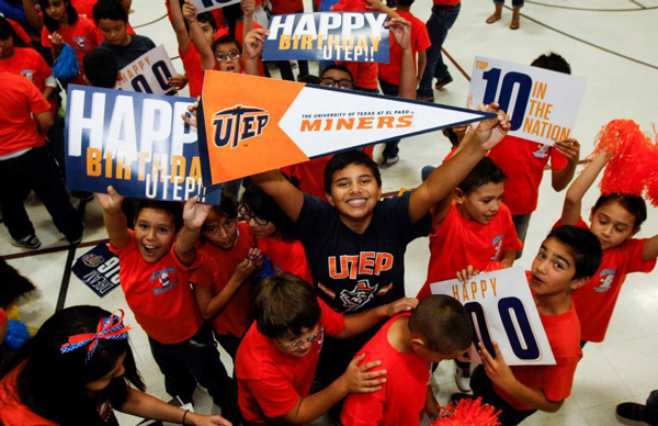 A young student smiles as he holds up a UTEP Miners banner. Photo by UTEP News Service