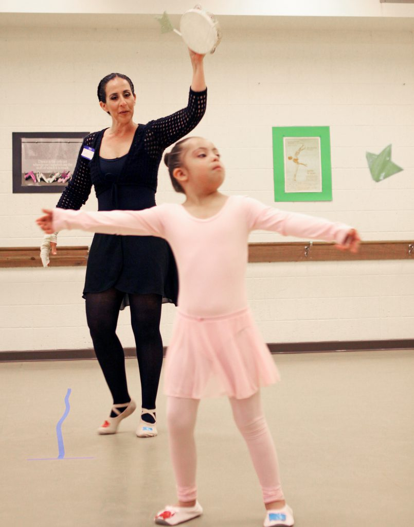 Laura Escobar encourages Ximena Fuentes with a ballet step during a class in the Fox Fine Arts Center. Escobar developed the eight-week course to give children with Down syndrome a fun and healthy outlet to enhance their quality of life. Photo by Laura Trejo / UTEP News Service