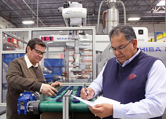Hector Lopez (right), a field engineer at the Texas Manufacturing Assistance Center, examines Plastic Molding Technology's production line with PMT quality assurance manager Martin Rubio. Photo by Laura Trejo / UTEP News Service