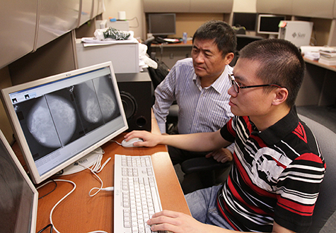 Wei Qian, Ph.D., left, professor of electrical engineering, is working with doctoral student Wenqing Sun to create a breast cancer prediction system. Photo by J.R. Hernandez / UTEP News Service