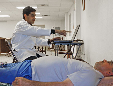 Master of Public Health student Juan Antonio Aguilera, M.D., (sitting) reviews Sam Ochoa's electrocardiogram during a free community health screening on Oct. 17.   Student researchers in UTEP's Master of Public Health and Health Promotion programs will offer free health exams to El Paso residents who are medically uninsured as part of a study with the City of El Paso. Photo by Laura Trejo / UTEP News Service