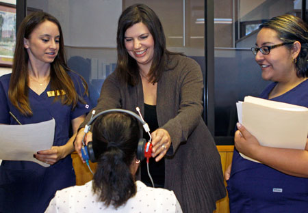 UTEP speech language pathology graduate students Blair Salome, left, and Magda Mena, right, observe as UTEP assistant professor Jamie Desjardins, center, screens health fair participants for hearing loss. Photo by Laura Trejo / UTEP Communications