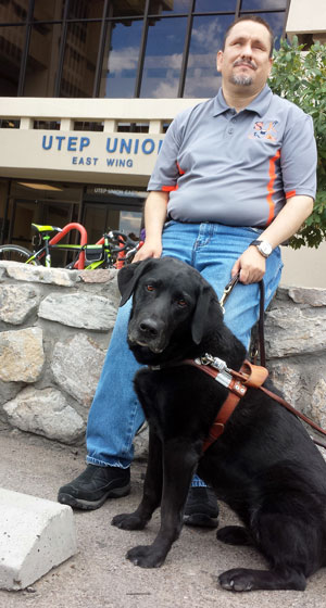 David Issac Valencia poses with his former service dog, Izzie, outside the UTEP Union Building. Izzie was recently retired and replaced by a yellow lab named Fonda, who is one of about 20 registered service animals on the UTEP campus. Photo by Daniel Perez / UTEP Communications